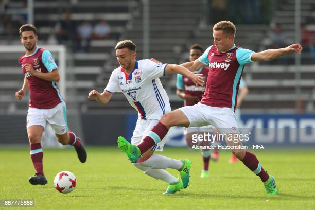 Amine Gouiri of Olympique Lyonnais is tackled by Luke Woolfenden of West Ham United during the match between West Ham United and Olympique Lyonnais...