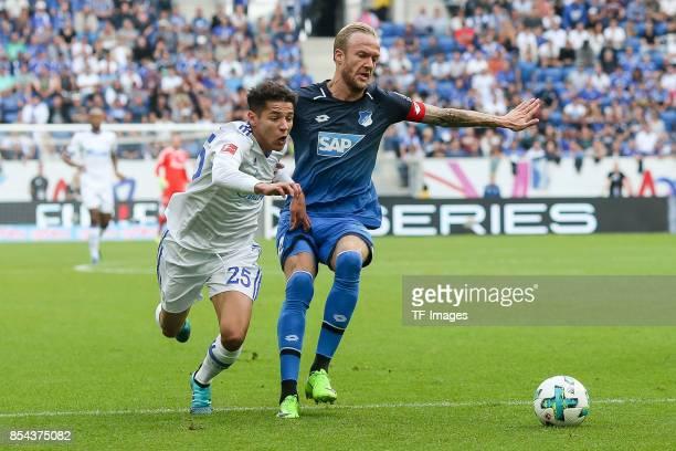Amine Harit of Schalke and Kevin Vogt of Hoffenheim battle for the ball during the Bundesliga match between TSG 1899 Hoffenheim and FC Schalke 04 at...