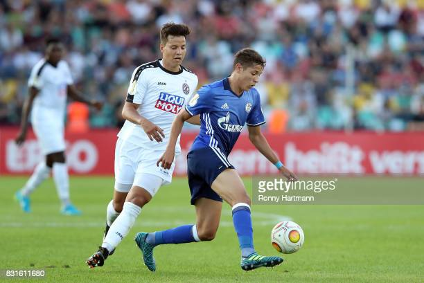Amine Harit of Schalke and Philip Schulz of Berlin vie during the DFB Cup first round match between BFC Dynamo and FC Schalke 04 at...