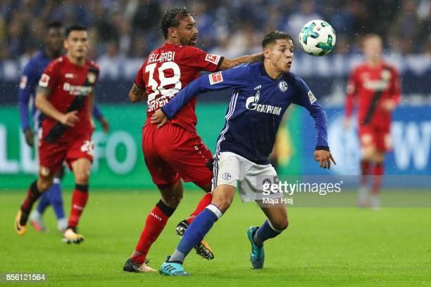 Amine Harit of Schalke and Wendell of Leverkusen battle for the ball during the Bundesliga match between FC Schalke 04 and Bayer 04 Leverkusen at...