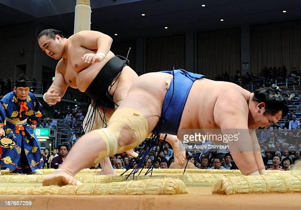 Aminishiki throws ozeki Kotoshogiku to win during day one of the Grand Sumo Kyushu Tournament at Fukuoka Convention Center on November 10 2013 in...