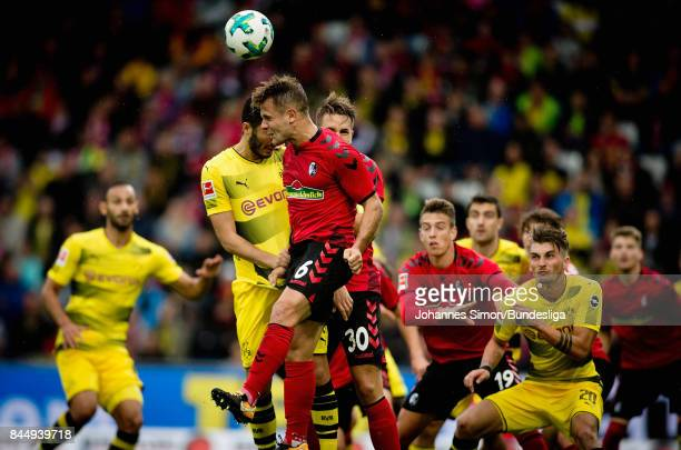 Amir Abrashi Christian Guenther of Freiburg and Nuri Sahin of Dortmund head for the ball during the Bundesliga match between SportClub Freiburg and...