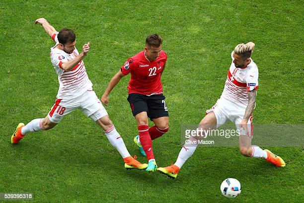 Amir Abrashi of Albania competes for the ball against Admir Mehmedi and Valon Behrami of Switzerland during the UEFA EURO 2016 Group A match between...