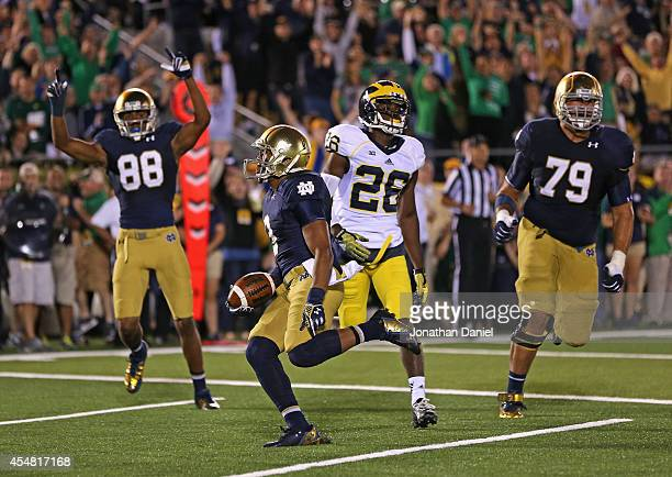 Amir Carlisle of the Notre Dame Fighting Irish scores a touchdown past teammates Steve Elmer and Corey Robinson and Jourdan Lewis of the Michigan...