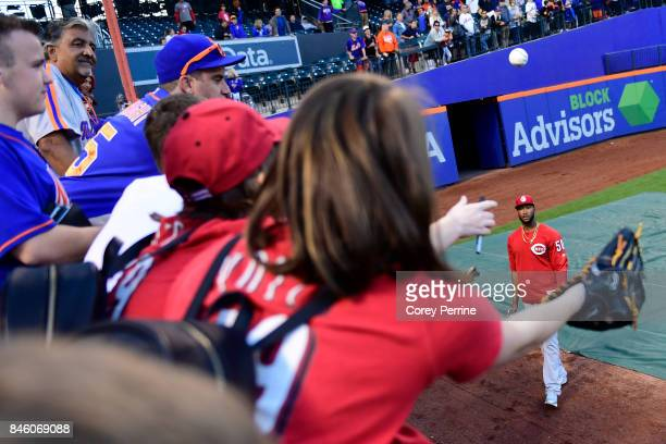 Amir Garrett of the Cincinnati Reds tosses a ball toward fans during batting practice before taking on the New York Mets at Citi Field on September 9...