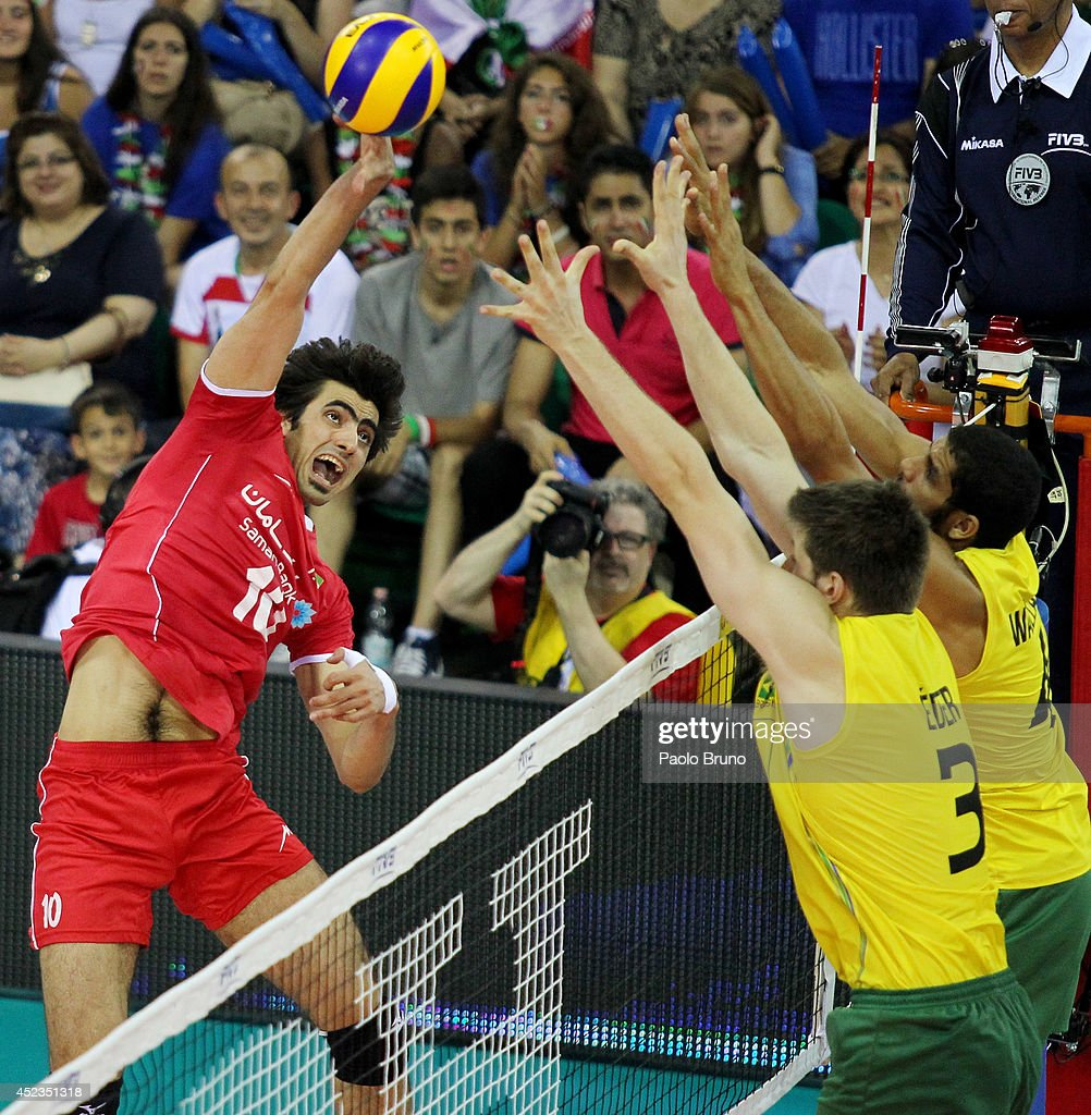 Amir Ghafour of Iran spikes the ball as Brazil players block during the FIVB World League Final Six match between Brazil and Iran at Mandela Forum on July 18, 2014 in Florence, Italy.