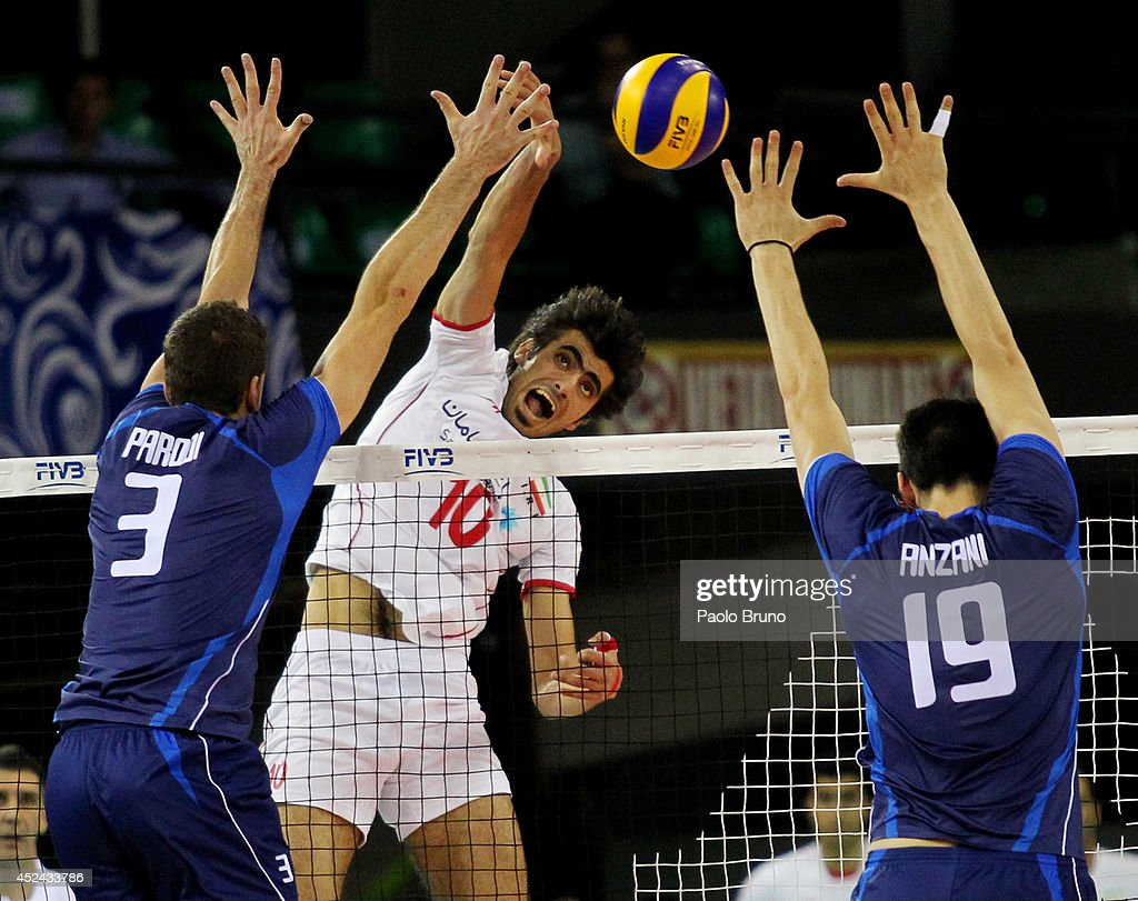 Amir Ghafour of Iran spikes the ball as Italy players block during the FIVB World League Final Six match for the third place between Iran and Italy at Mandela Forum on July 20, 2014 in Florence, Italy.
