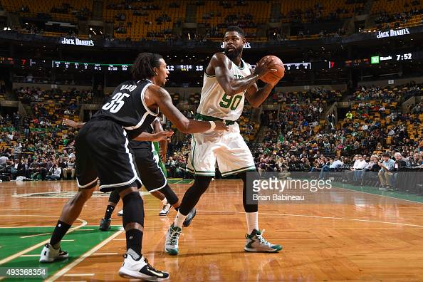 Amir Johnson of the Boston Celtics defends the ball against Justin Harper of the Brooklyn Nets during the preseason game on October 19 2015 at TD...