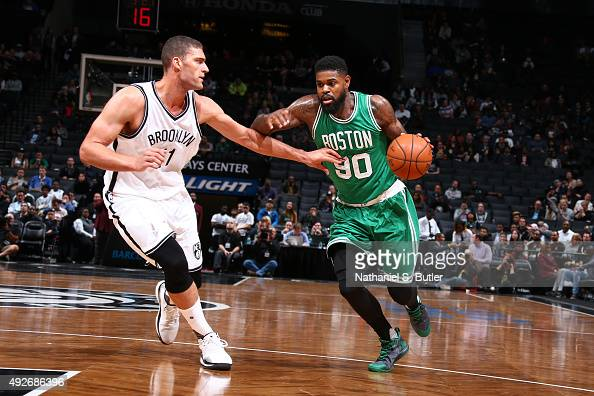 Amir Johnson of the Boston Celtics drives to the basket against Brook Lopez of the Brooklyn Nets during the preseason game on October 14 2015 at...