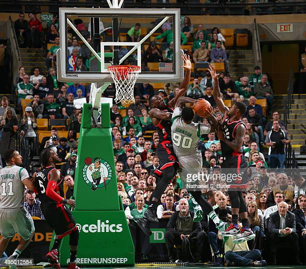 Amir Johnson of the Boston Celtics goes up to shoot against Bismack Biyombo of the Toronto Raptors and Terrence Ross of the Toronto Raptors during a...