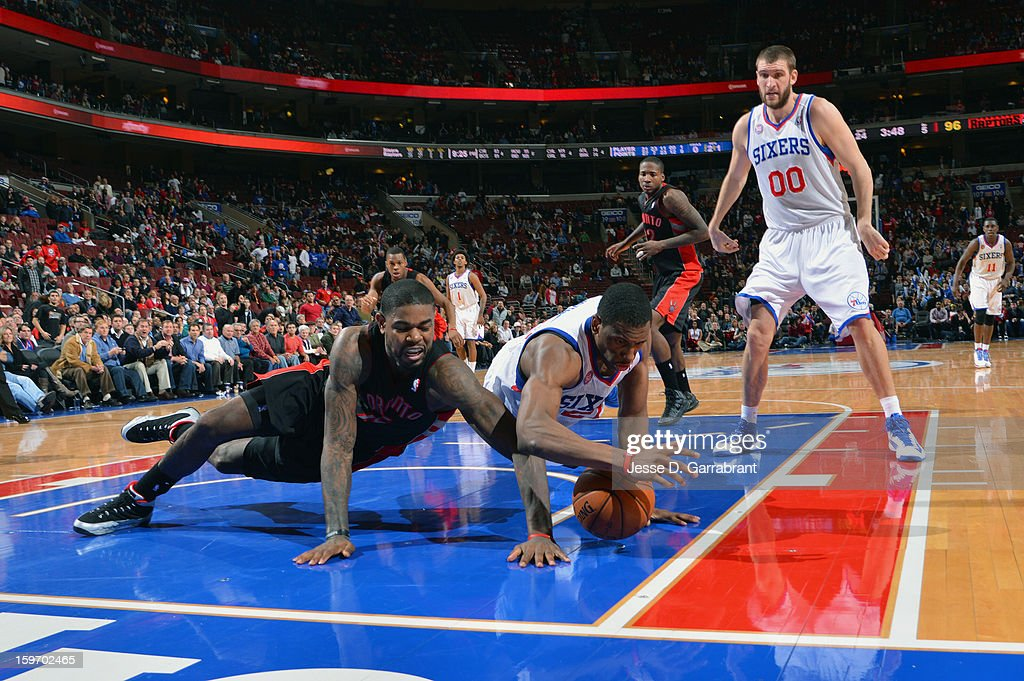 Amir Johnson #15 of the Toronto Raptors and Thaddeus Young #21 of the Philadelphia 76ers reach for the ball during the game at the Wells Fargo Center on January 18, 2013 in Philadelphia, Pennsylvania.