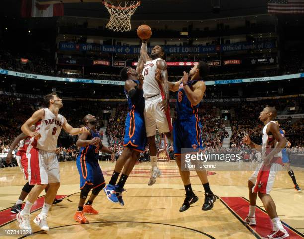 Amir Johnson of the Toronto Raptors attempts the dunk over Amar'e Stoudemire and Landry Fields of the New York Knicks during a game on December 5...