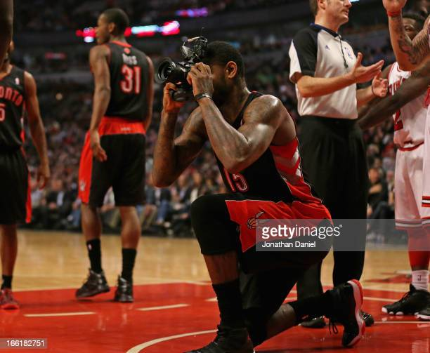 Amir Johnson of the Toronto Raptors pretends to take a picture with a remote camera that was kicked onto the floor during a game against the Chicago...