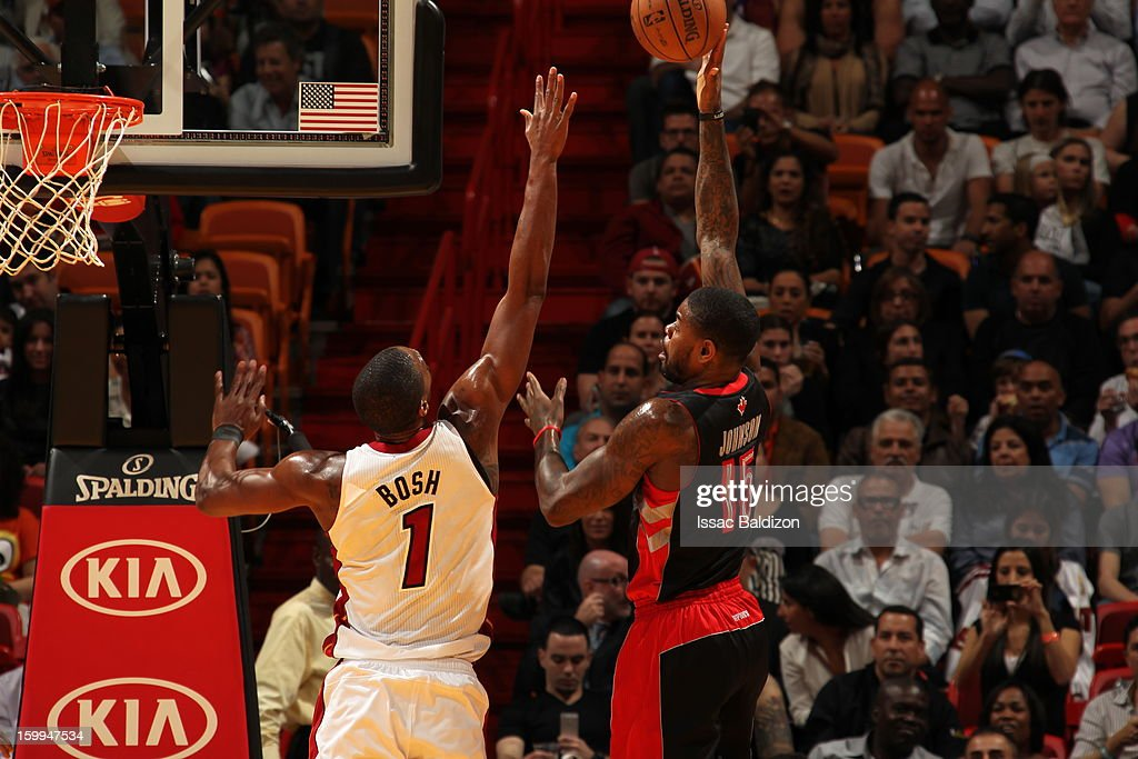 Amir Johnson #15 of the Toronto Raptors shoots over Chris Bosh #1 of the Miami Heat on January 23, 2013 at American Airlines Arena in Miami, Florida.