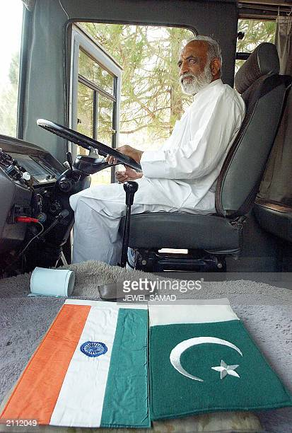 Amir Khan a Pakistani driver who will drive the first bus from Lahore to Delhi sits on behind the wheelnext to two national flags of India and...