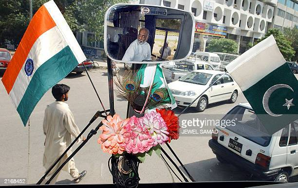 Amir Khan a Pakistani driver who will drive the first bus from Lahore to Delhi is reflected on a rearview mirror decorated with national flags of...