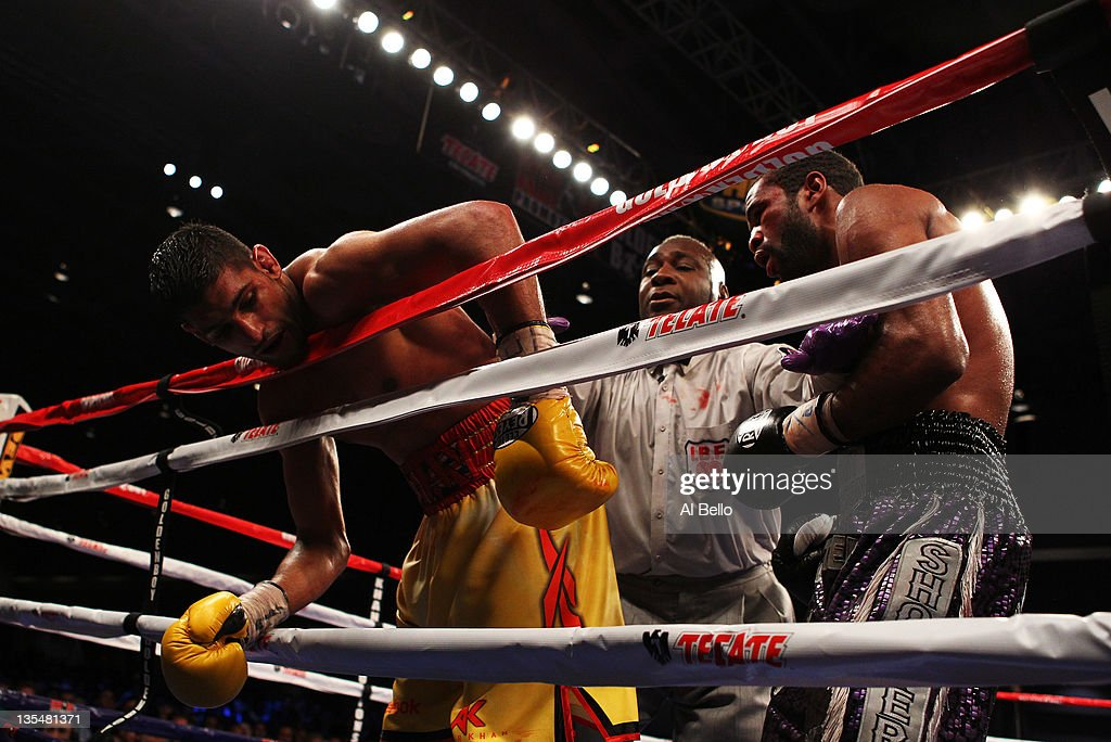 Amir Khan hangs over the ropes as Lamont Peterson is held back by referee Joe Cooper during their WBA Super Lightweight and IBF Junior Welterweight...