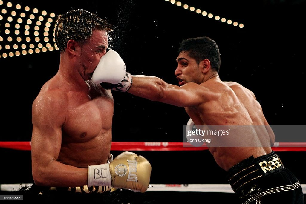 Amir Khan of Great Britain hits with a left to the face of Paulie Malignaggi during the WBA light welterweight title fight at Madison Square Garden...