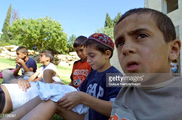 Amir Salum a 6yearold Palestinian and Israeli Daniel Shragai join friends as they listen to a storyteller who tells stories in Hebrew and Arabic July...