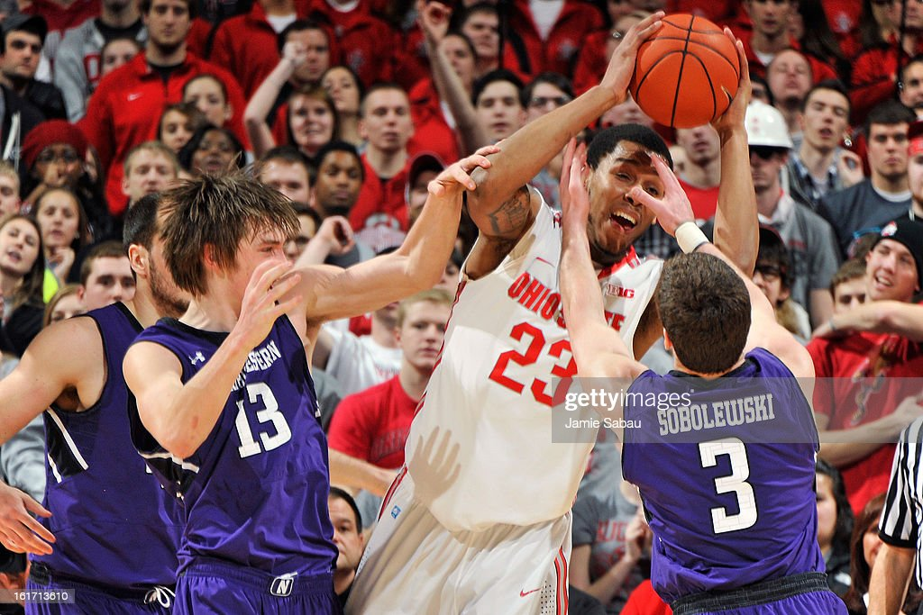 Amir Williams #23 of the Ohio State Buckeyes grabs an offensive rebound in the first half as Kale Abrahamson #13 of the Northwestern Wildcats and Dave Sobolweski #3 of the Northwestern Wildcats defend on February 14, 2013 at Value City Arena in Columbus, Ohio.