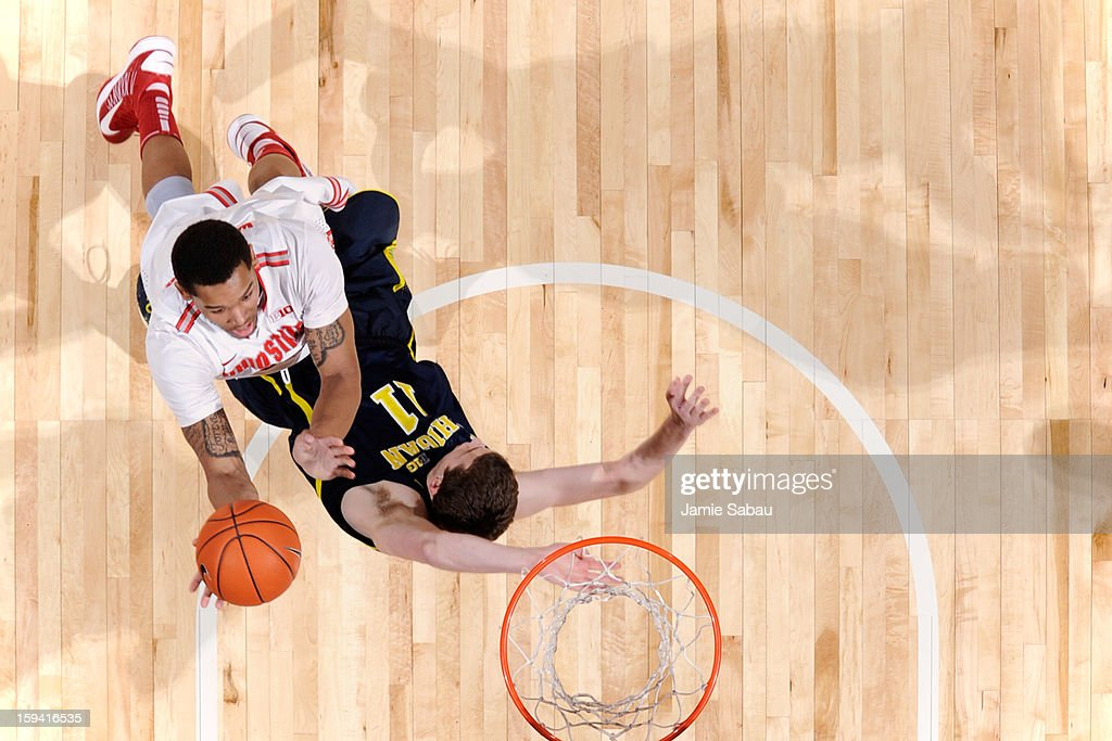 Amir Williams #23 of the Ohio State Buckeyes lays in the ball for two points in the second half despite being fouled by Nik Stauskas #11 of the Michigan Wolverines on January 13, 2013 at Value City Arena in Columbus, Ohio. Ohio State defeated Michigan 56-53.