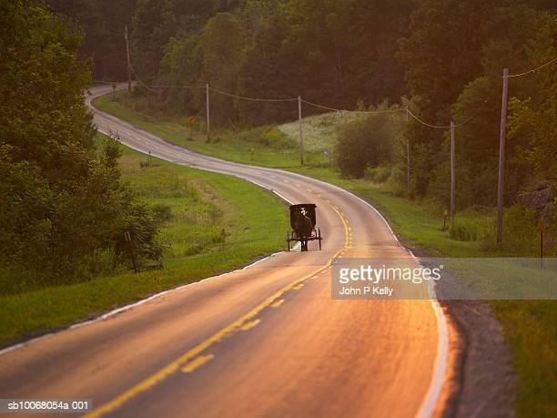 Amish horse-drawn wagon drives along rural road