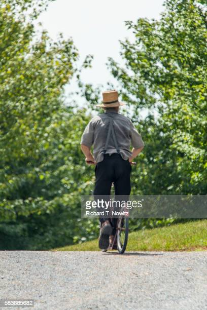Amish man pushes a scooter on country road