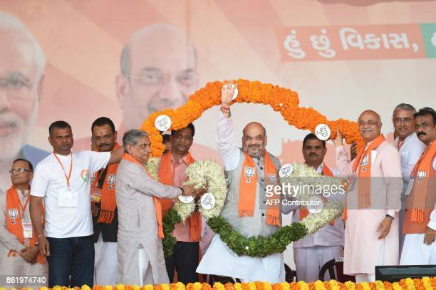 Amitbhai Shah President of Bhartiya Janta Party waves while being garlanded in rose petals in the formation of a map of Gujarat State during Gujarat...