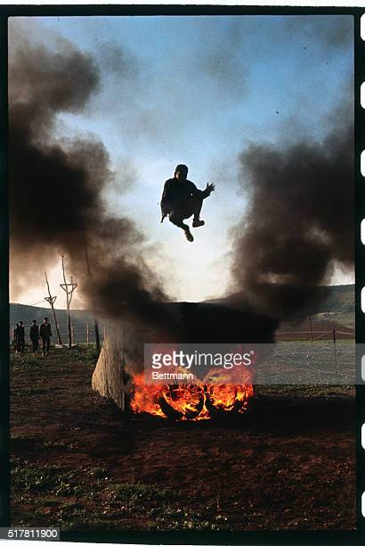 A youngster training to be a commando leaps over a fire at training camp run by AlFatah organization near the refugee camp at Baqa