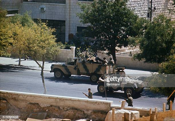 Jordanian army troops move through an Amman street with a camouflaged armored car during the height of the fighting against the Palestinian...