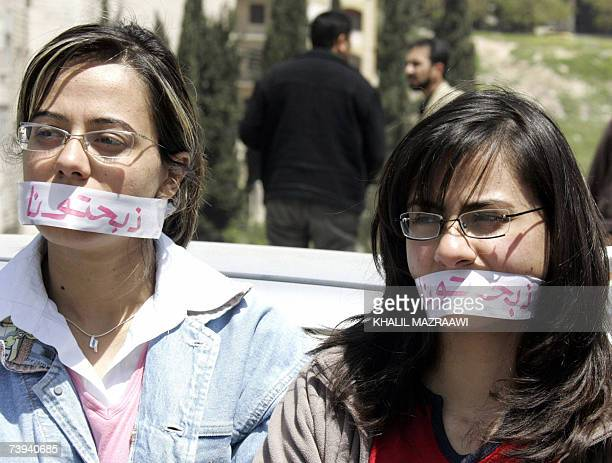 Jordanian university students cover their mouths with tape that reads 'you have slaughtered us' to protest against the increase in university fees...