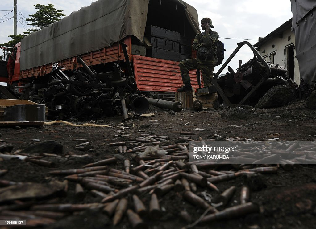 Ammunition remains on the ground at the former Congolese army headquarters in Goma on November 23, 2012 as a rebel soldier talks on his phone next to a truck carrying government munitions that the M23 rebel group captured from fleeing government troops when M23 took the regional capital Goma on November 20. The M23 rebel group, army mutineers who took the regional capital Goma on November 20 and the key town of Sake the next day, appeared to halt their rampant advance just south of Sake after battles with government forces and an allied local militia, a United Nations source told AFP. Thousands of people were fleeing Sake heading east toward Goma, and the local head of a relief agency reported numerous casualties.