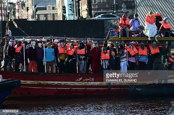 TOPSHOT Amnesty International activists hold a protest against the ongoing migrant crisis with a boat filled with mannequins wearing life vests...