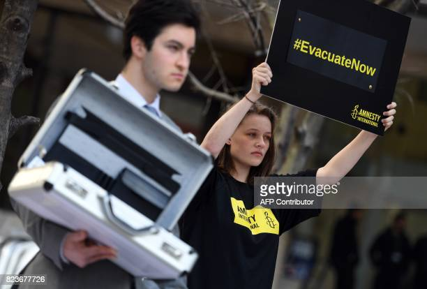 Amnesty International activists protest outside the Spanish corporate giant Ferrovials Australian headquarters in Sydney on July 28 2017 Ferrovial is...
