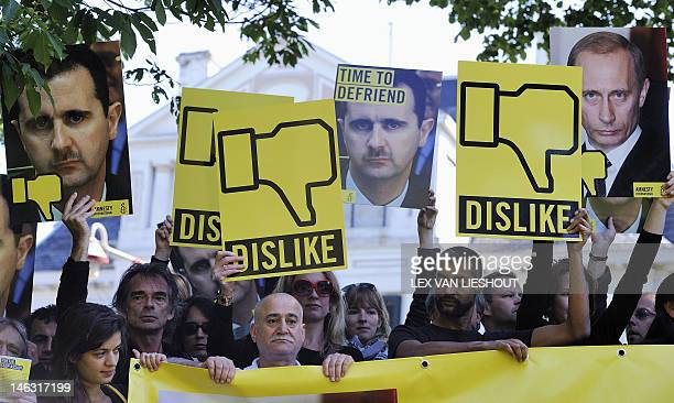 Amnesty International activists take part in a demonstration calling for an end to violence in Syria and an end to Russian President Vladimir Putin's...