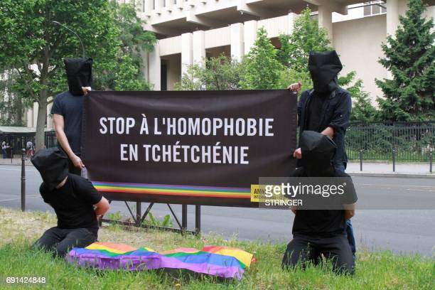 Amnesty International militants hold a banner reading 'Stop homophobia in Chechnya' to denounce persecution against the LGBT community in Chechnya on...
