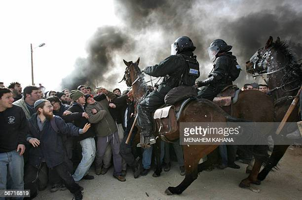 Israeli mounted policemen disperse settlers 01 February 2006 during clashes which erupted during the evacuation of the West Bank outpost of Amona...
