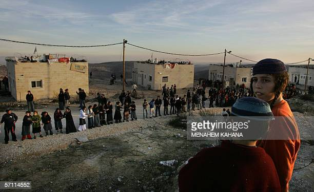 Israeli settler youth pass along building material while others stack a barrier as they hunker down prior to the army's planned destruction of nine...