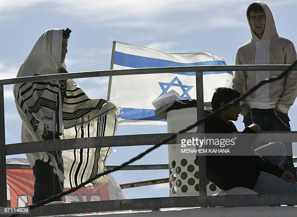 The Israeli flag flutters as settlers one in a prayer shawls or Talit bunker down on the roof of one of the nine houses marked for destruction in the...