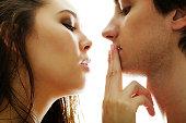 Pretty brunette touching male lips by her fingers