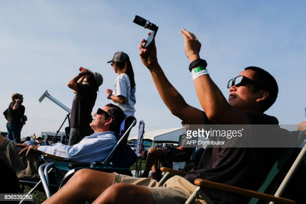 Amos Yew right uses a lens on an iPhone to record video in the first stages of the total solar eclipse Monday August 21 2017 in Madras Oregon / AFP...