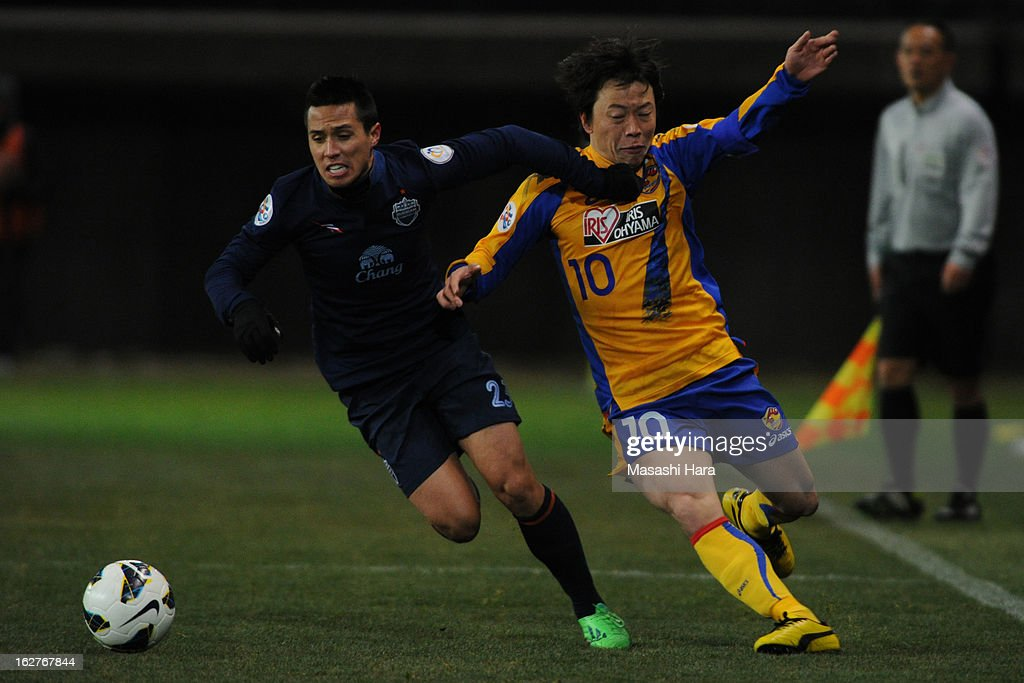 Ampaipitakwong #23 of Buriram United (L) and Ryang Yong Gi #10 of Vegalta Sendai compete for the ball during the AFC Champions League Group E match between Vegalta Sendai and Buriram United at Sendai Stadium on February 26, 2013 in Sendai, Japan.