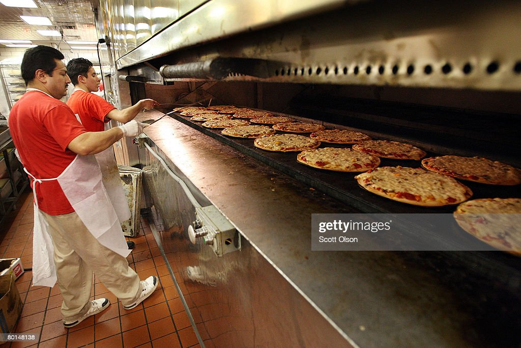 Amparo Perez (L) and Adrian Reyes remove pizzas from an oven at Connie's Pizza on March 6, 2008 in Chicago, Illinois. The cost of flour, a key ingredient in making pizza dough, has more than doubled in the past year because of high wheat prices caused by strong worldwide demand and increased price speculation. Connie's Pizza makes between 10 to 20 thousand pizzas each week.