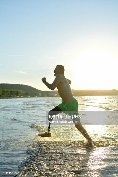 Amputee man running in a lake at sunset