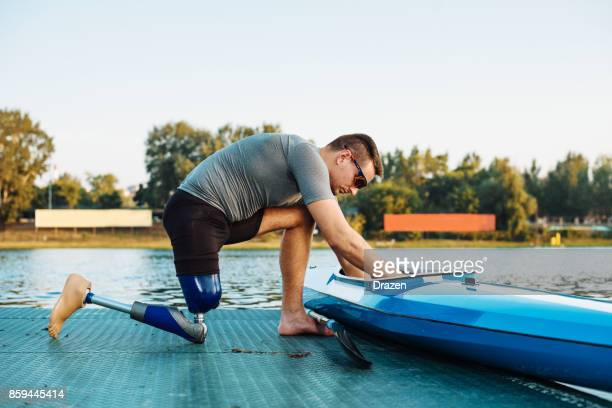 Amputee sportsman adjusting his kayak for training