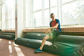 Full length portrait of young  amputee sportsman sitting by window in modern gym, copy space