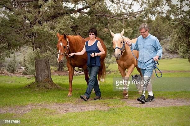 Amputee w/wife, leading horses down a path