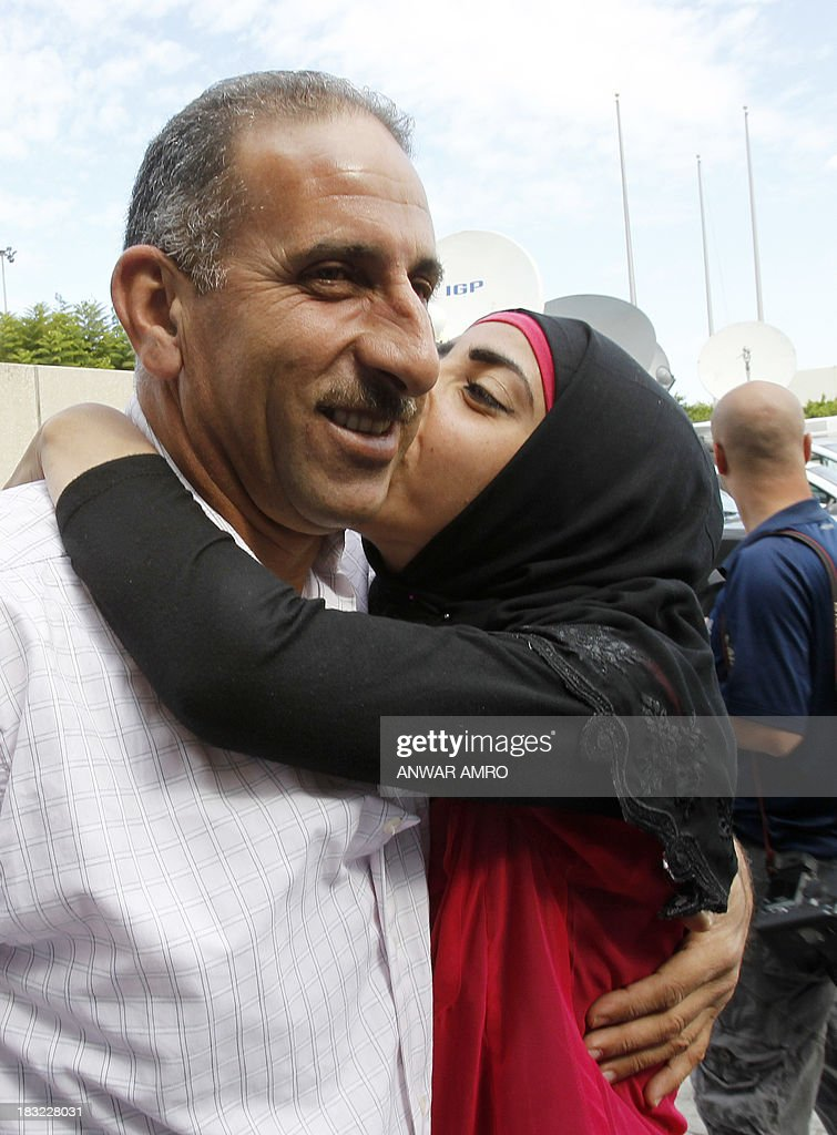 Amra Hassan (L), a Lebanese survivor of the migrant shipwreck in Indonesia last week, is kissed by a relative as he arrives at Beirut airport on October 6, 2013. Lebanese asylum-seekers who died when a boat sank off Indonesia were the victims of people smugglers who prey on them and Syrian refugees seeking to better their lives.