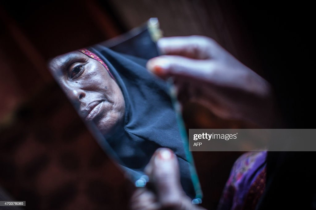 Amran Mahamood who has made a living for 15 years by circumcising young girls looks into a piece of a mirror on February 19 2014 in Hargeysa The...