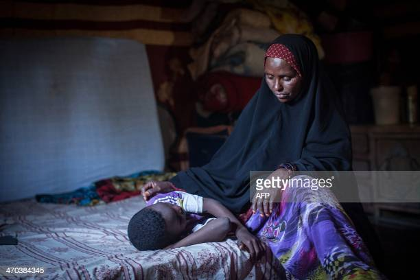 Amran Mahamood who has made a living for 15 years by circumcising young girls sits next to a girl on February 19 2014 in Hargeysa Four years ago she...